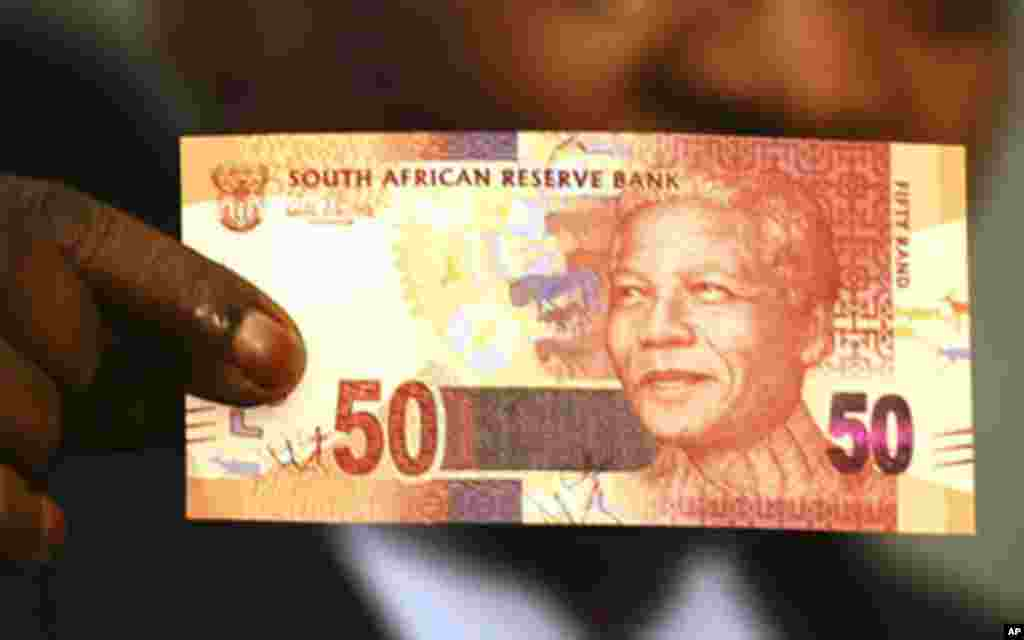 South Africa's President Jacob Zuma holds up a banknote bearing the face of former president Nelson Mandela in Pretoria February 11, 2012.