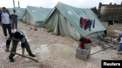 Syrian refugees shovel away water pooled outside their tents after heavy rain, at a center funded by the International Islamic Relief Organization of Saudi Arabia (IIROSA), which provides shelter for Syrian refugees in al-Marj, in the Bekaa valley, Lebanon, January 7, 2013.