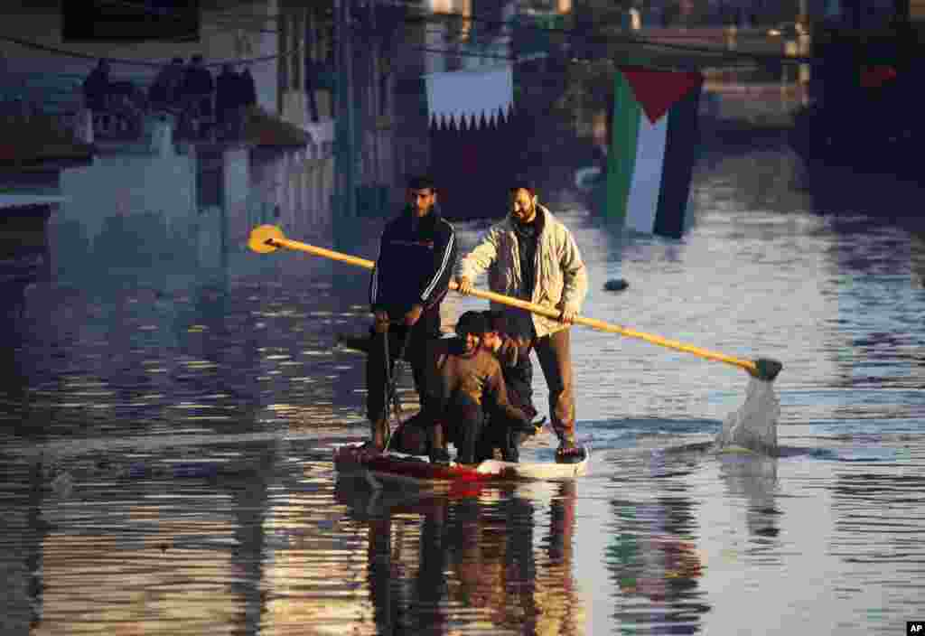 Palestinian rescue volunteers ride a boat with residents in Gaza City. Rescue workers evacuated thousands of Gaza Strip residents from homes flooded by heavy rain, using fishing boats and heavy construction equipment to pluck some of those trapped on upper floors.