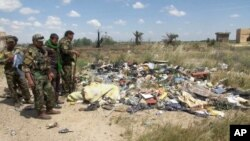 In this image made from video, Iraqi Shi'ite militiamen stand near a mass grave, believed to contain the bodies of Iraqi soldiers killed by Islamic State group militants when they overran Camp Speicher military base last June, in Tikrit, Iraq, April 2, 20