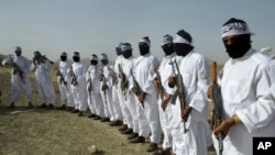 FILE - Taliban suicide bombers stand guard during a gathering of a breakaway Taliban faction, in the border area of Zabul province, Afghanistan. Eighteen bombers in training were killed in a recent airstrike in the province, Afghan officials say.