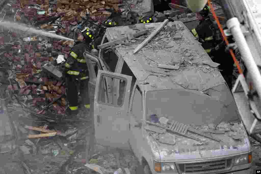 Bombeiros no local onde um prédio explodiu e outro acabou colapsar também em Harlem, Nova Iorque, Março 12, 2014.