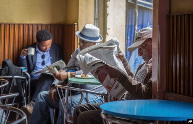 FILE - In this Oct. 10, 2016, photo, Ethiopian men read newspapers and drink coffee at a cafe during a declared state of emergency in Addis Ababa, Ethiopia. Since 2015 there have been wide-ranging internet shutdowns.