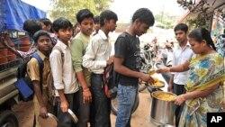 2012年1月10号在一所政府开设的高中里,一位老师在为学生分午餐。