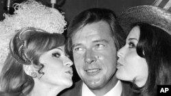 Roger Moore reçoit un baiser de Miss Grande Bretagne et de Miss USA à Londres, le 4 novembre 1971.
