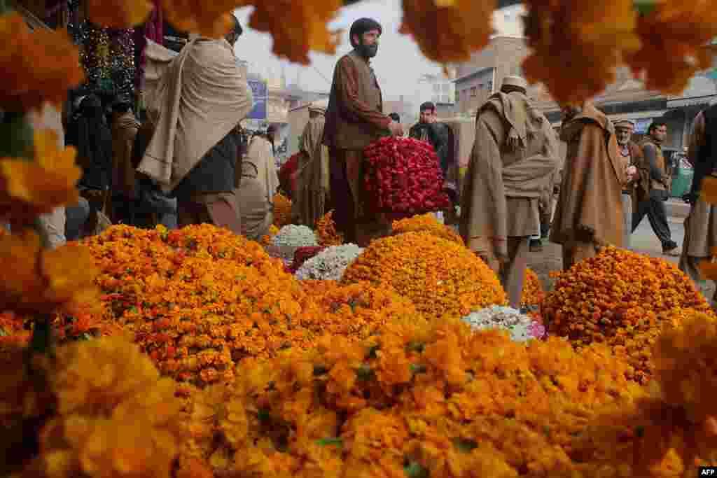 Para penjaja bunga menjual karangan bunga di Peshawar, Pakistan.