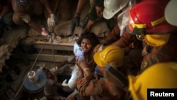 FILE - Rescue workers pull a garment worker from the rubble of a collapsed building outside of Dhaka April 27, 2013.