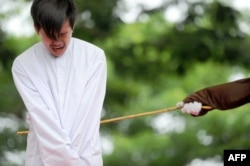 FILE - One of two Indonesian men is publicly caned for having sex, in a first for the Muslim-majority country where there are concerns over mounting hostility towards the small gay community, in Banda Aceh, May 23, 2017.