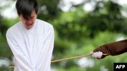 Salah satu dari dua orang Indonesia yang dicambuk di depan umum di Banda Aceh, karena berhubungan seks sesama jenis, 23 Mei 2017.