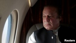 FILE - Pakistani Prime Minister Nawaz Sharif looks out the window of his plane after attending a ceremony to inaugurate the M9 motorway between Karachi and Hyderabad, Pakistan. Prime Minister Nawaz met Monday with Saudi King Shah Salman bin Abdul Aziz in Jeddah, but no progress was reported in resolving the crisis.