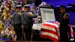 Law enforcement officer salute Dallas Police Sr. Cpl. Lorne Ahrens before his funeral service at Prestonwood Baptist Church in Plano, Texas, July 13, 2016.