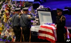 FILE - Law enforcement officer salute Dallas Police Sr. Cpl. Lorne Ahrens before his funeral service at Prestonwood Baptist Church in Plano, Texas, July 13, 2016.