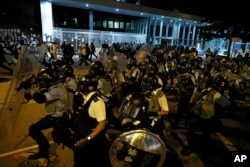 Police officers in anti-riot gear clear protesters from the Legislative Council in Hong Kong, during the early hours of Tuesday, July 2, 2019. (AP Photo/Vincent Yu)