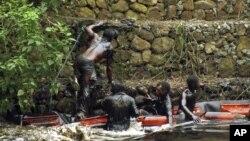 En esta foto tomada el 7 de febrero de 2012, trabajadores intentan contener un derrame de petróleo en el río Guarapiche, en las afueras de Maturin, Venezuela.
