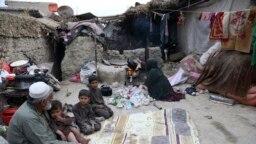 Yousuf, yang melarikan diri bersama keluarganya dari rumahnya di Afghanistan timur delapan tahun lalu untuk menghindari perang, duduk bersama anak-anak sementara istrinya membakar plastik saat dia membuat teh, di Kabul, Afghanistan. (Foto: AP//Rahmat Gul)