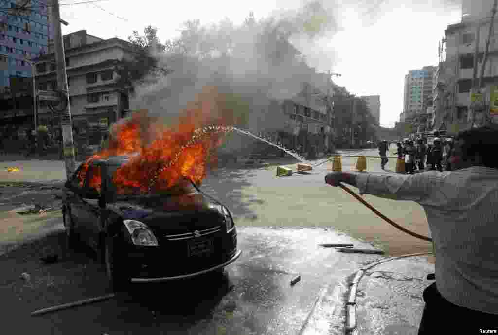 A man sprays water on a car set on fire by activists of the Jemaat-e-Islami party protesting the revised sentencing of Abdul Quader Mollah, Dhaka, Sept. 17, 2013.
