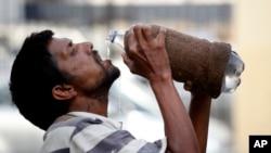 Seorang pria minum air dari botol di tengah hari yang terik di Allahabad, India (31/5). (AP/Rajesh Kumar Singh)