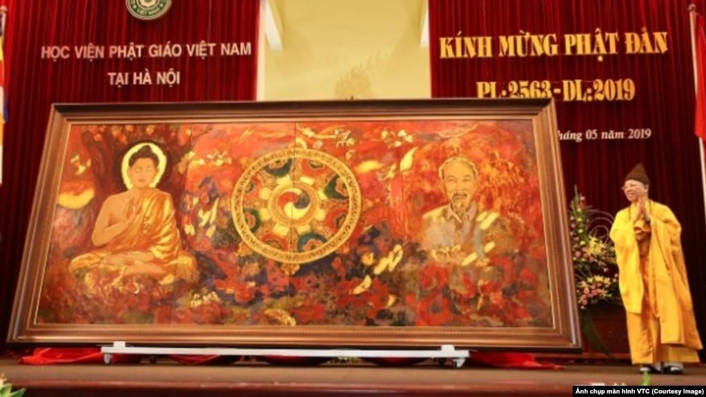 """Thượng tọa Thích Thanh Quyết, cũng là đại biểu Quốc hội Việt Nam, giới thiệu bức tranh """"Đạo pháp và dân tộc"""" tại một buổi lễ mừng ngày sinh của Đức Phật tại Học viện Phật giáo ở Sóc Sơn, Hà Nội, hôm 10/5. (Ảnh chụp màn hình VTC)"""