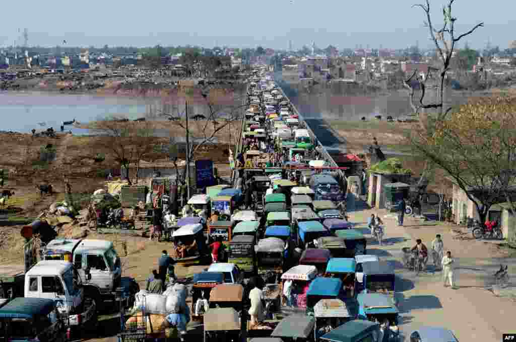 在巴基斯坦的拉合爾,前來上班的人們在進入這座城市的橋上陷入擁堵。