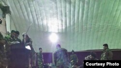 FILE - Prisoners freed from Taliban prisons in Helmand dine at an Afghan military facility.