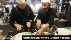 Chef of the Hotel d'Angleterre, Michael Coquelle, left, and Chef Nadeem Khadem al-Jamie, who is also a Syrian refugee, work together in the hotel's kitchen for the Refugee Food Festival, Oct. 11, 2017.
