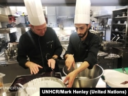 Chef of the Hotel d'Angleterre, Michael Coquelle, left, and Chef Nadeem Khadem Al Jamie, who is also a Syrian refugee, work together in the hotel's kitchen for the Refugee Food Festival, Oct. 11, 2017.