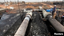 FILE - Oil engineers work on a main oil pipeline in Heglig oilfield, May 2, 2012.