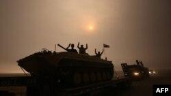 Tentara Irak mengacungkan dua jari tanda kemenangan saat berkendara melewati daerah al-Shura, arah selatan Mosul (24/10). (AFP/Ahmad al-Rubaye)