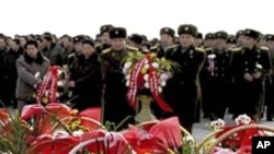 Warga Korea Utara dan tentara meletakkan karangan bunga tanda penghormatan mereka terhadap mendiang pemimpin mereka Kim Il-sung and Kim Jong-il di Mansu Hill dalam peringatan setahun wafatnya Kim Jong-il di Pyongyang, Korea Utara (16/12).