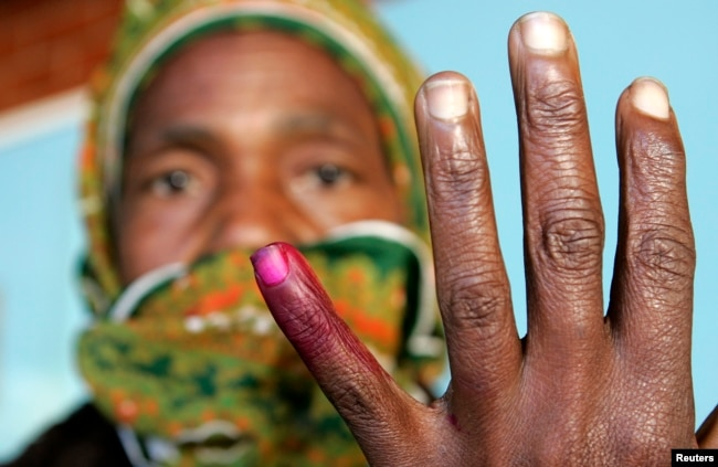 FILE - A woman shows her ink-stained finger after voting in Zimbabwe's presidential and parliamentary elections in Harare, March 29, 2008.