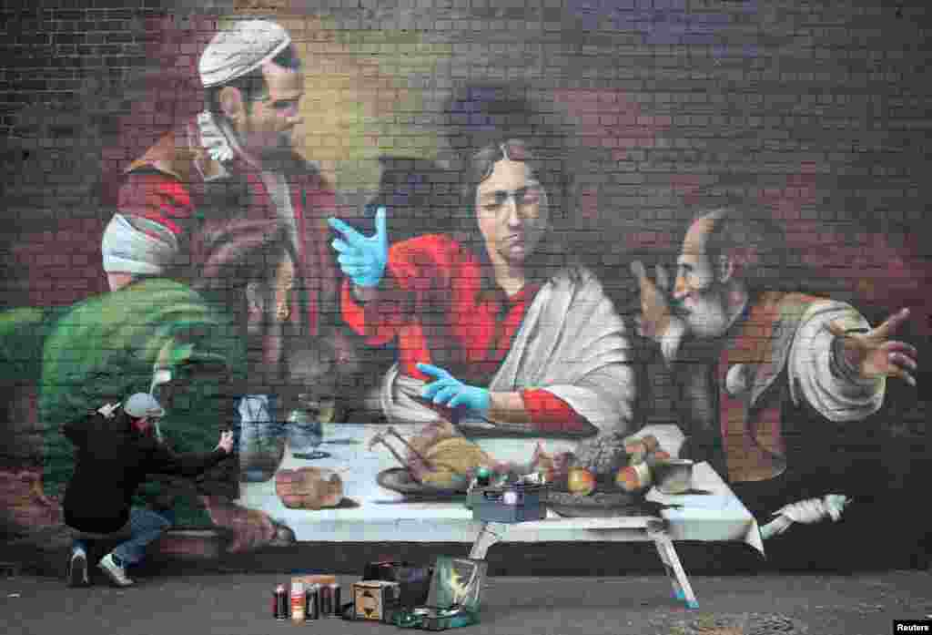Artist Lionel Stanhope paints a mural in Ladywell depicting the Supper at Emmaus by Caravaggio with added protective gloves, in London.