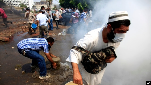 Supporters of Egypt's ousted President Mohammed Morsi clash with the Egyptian security forces as the forces clear their sit-in camp in the eastern Nasr City district of Cairo, Aug. 14, 2013.