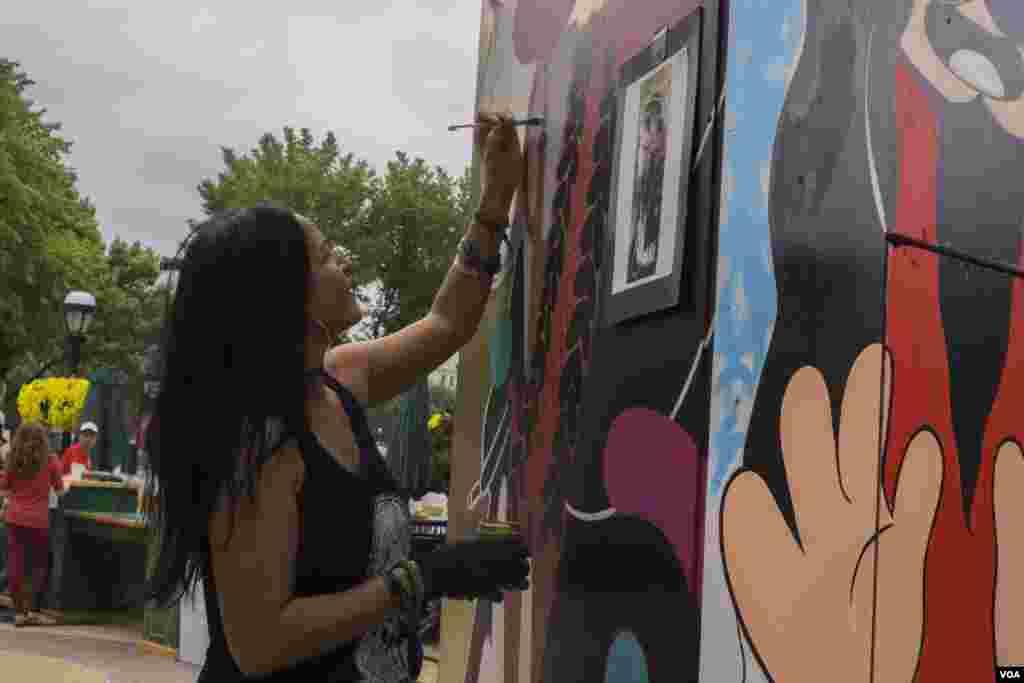 Художник и дизайнер Сита Садели работает над картиной. Часть картины, над которой она работает, сочетает орнаменты, используемые на танцорами на о.Ява, Индонезия (Фото: Т. Харт / VOA)