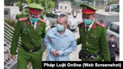 Bị cáo Lê Đình Công bị công an áp giải đến phiên toà phúc thẩm ở Hà Nội diễn ra từ 8-9/3 trong vụ xét xử kháng cáo liên quan đến cuộc đột kích vào làng Đồng Tâm ở Mỹ Đức ngày 9/1/2020 vì tranh chấp đất đai giữa chính quyền và người dân. (Ảnh chụp màn hình Pháp Luật Online)