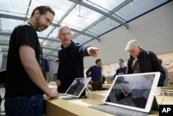 Apple CEO Tim Cook points out the new 9.7 inch iPad Pro to a customer during a visit to the Apple Store, in Palo Alto, California, March 31, 2016..