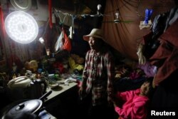 Migrant worker Wang Qin and her 10-year-old granddaughter Feng Aobin sit in their one-room home at the outskirts of Beijing, Oct. 1, 2017.