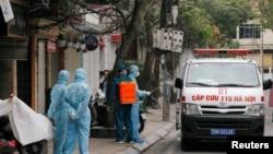 Tẩy rửa một xe cứu thương gần nhà một người nhiễm virus corona tại Hà Nội, 7 tháng Ba. (REUTERS)