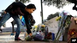 Faith Reyna leaves flowers at a make-shift memorial for slain San Antonio police officer Benjamin Marconi, 50, a 20-year veteran of the force, Nov. 21, 2016. Marconi was fatally shot during a traffic stop near police headquarters Nov. 20, 2016.