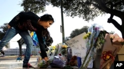 费思·雷纳把鲜花放在遇害的圣安东尼奥警察本杰明·马克尼的临时纪念地。(2016年11月21日)