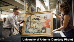 University of Arizona staff members prepare to examine Willem de Kooning's work after it was returned to the school.