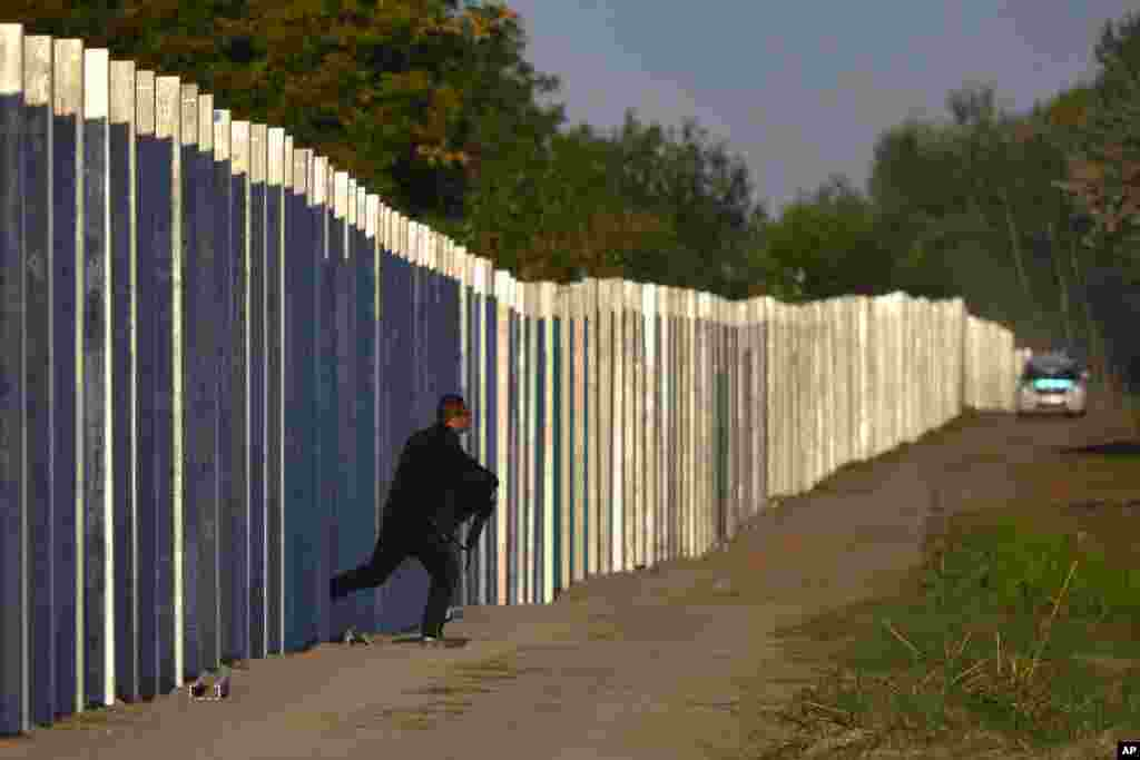 A migrant runs after he entered the territory of Hungary by crossing the temporary protection fence along the Hungarian-Serbian border as a Hungarian police car approaches at Roszke, 180 kms southeast of Budapest, Sept. 7, 2015.