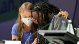 Ugandan climate activist Vanessa Nakate, right, is comforted by Swedish activist Greta Thunberg as she is overcome by emotion after speaking at the opening of a three-day Youth for Climate summit in Milan, Italy, Tuesday, Sept. 28, 2021. (AP Photo/Luca Br