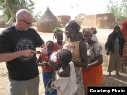 Dave Stahl helps children pump their soccer balls in Niger. (Courtesy Project Play Africa)