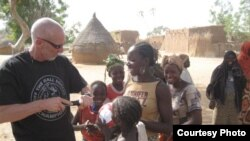Dave Stahl helps children pump their soccer balls in Niger