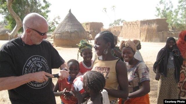Dave Stahl helps children pump their soccer balls in Niger