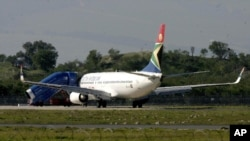 A South African Airways plane is parked at the end of the runway after returning to the airport in Cape Town, South Africa, Saturday June 17, 2006. A 21-year-old man was arrested after trying to force his way into the cockpit shortly after takeoff on flig