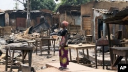 A woman stands in front of burnt buildings in Kachia village, where violence erupted last week, in Nigeria's northern state of Kaduna, April 28, 2011