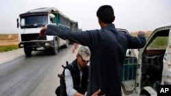 Kürd polis işçisi ABŞ-ın dəstəklədiyi nəzarət-buraxılış məntəqəsində suriyalı ərəb üzərində axtarış aparır. 28 mart, 2018.