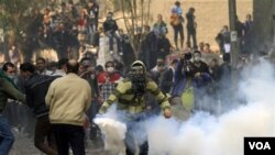 Seorang pengunjuk rasa berlari untuk membuang gas air mata dalam bentrokan dengan polisi mesir di lapangan Tahrir, Cairo, Mesir (22/11).