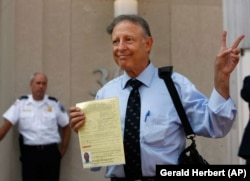 Dick Heller, who sued to overturn Washington handgun ban, poses for the media after picking up his gun registration, Monday, Aug. 18, 2008 at Washington's Metropolitan Police headquarters. (AP Photo/Gerald Herbert)